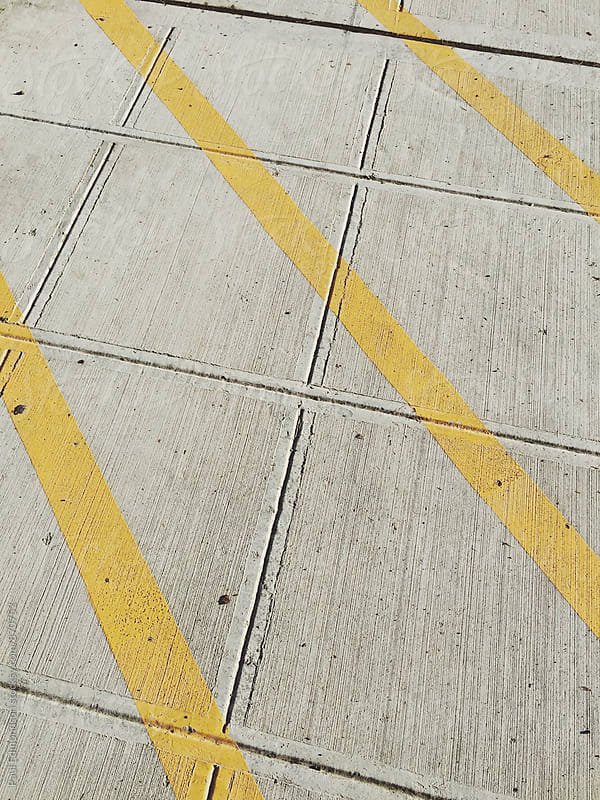 Yellow boundary lines one urban sidewalk, close up by Paul Edmondson for Stocksy United