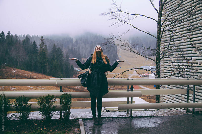 Young woman in the mountains enjoying the rain by Maja Topcagic for Stocksy United