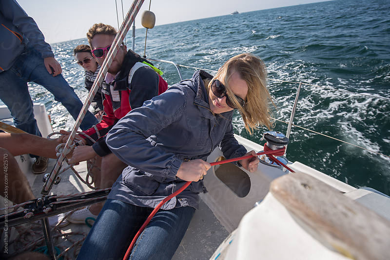 Woman and crew on sail boat working together on rigging for ocean adventure by Jonathan Caramanus for Stocksy United