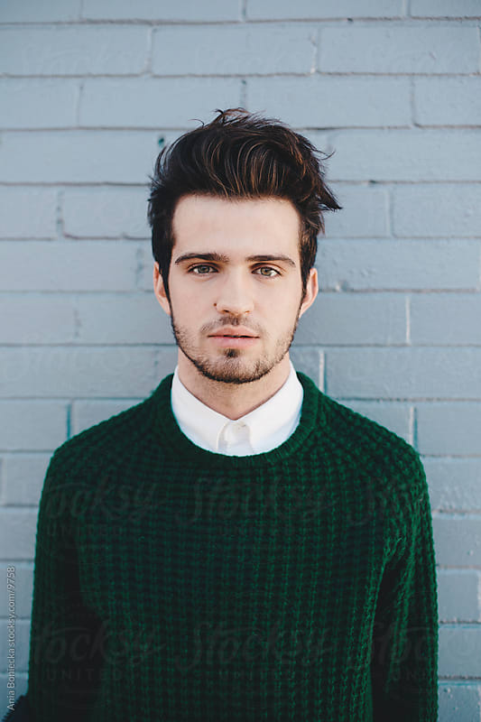 A portrait on a man in a green sweater by Ania Boniecka for Stocksy United