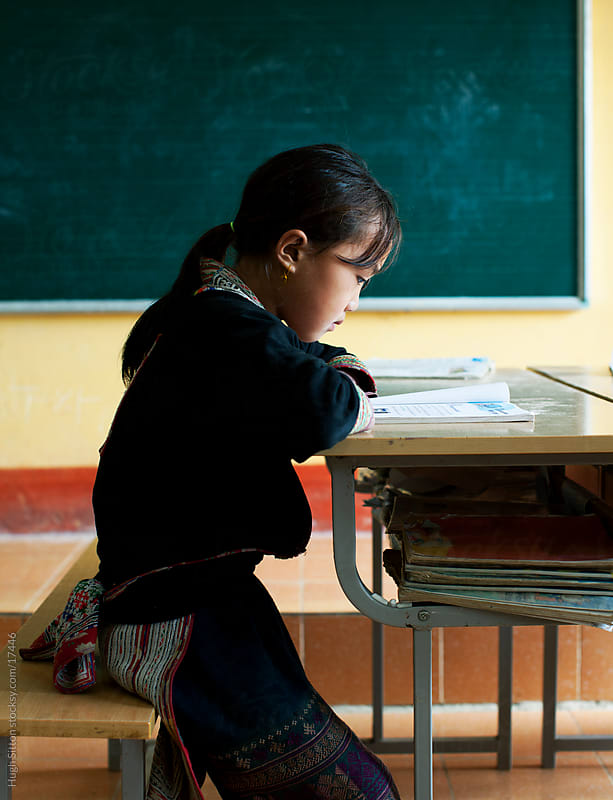 Young girl from Hmong tribe, studying alone in classroom. Sapa. by Hugh Sitton for Stocksy United