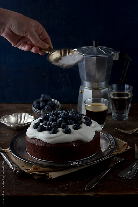 Chocolate cake topped with beaten cream and blueberries by Noemi Hauser for Stocksy United