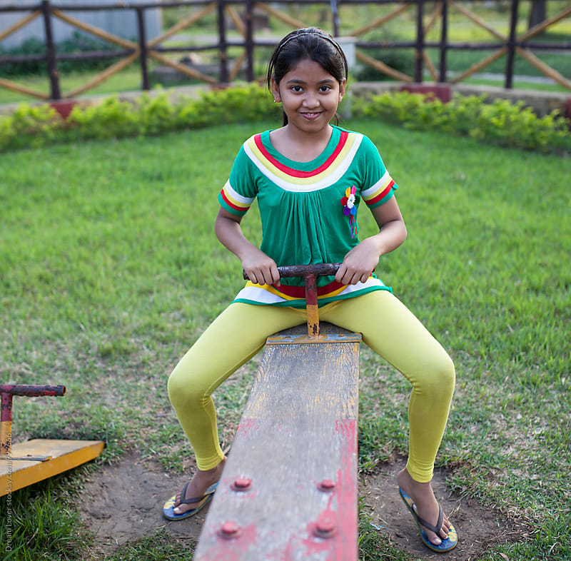A girl plays in a park alone  by PARTHA PAL for Stocksy United