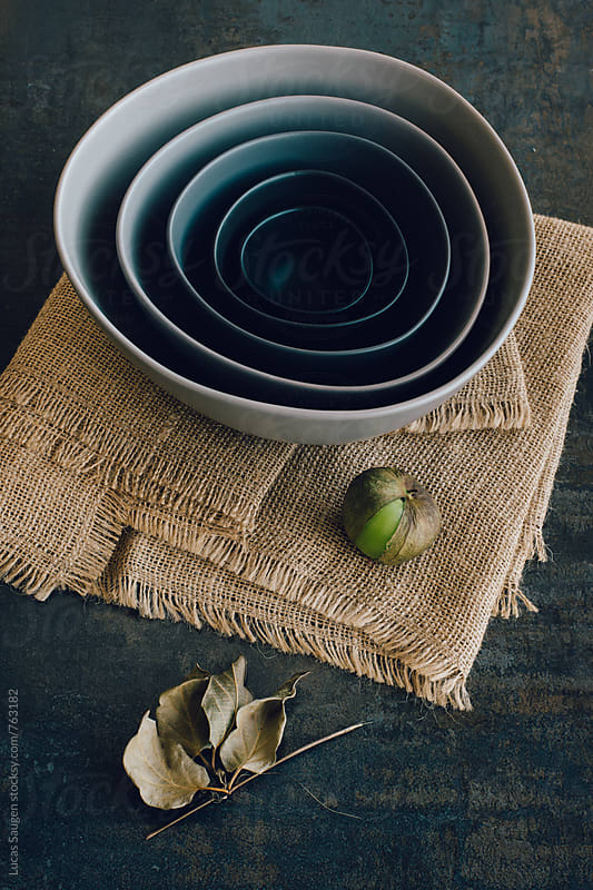 A group of bowls stacked neatly and propped with a tomatillo.  by Lucas Saugen for Stocksy United
