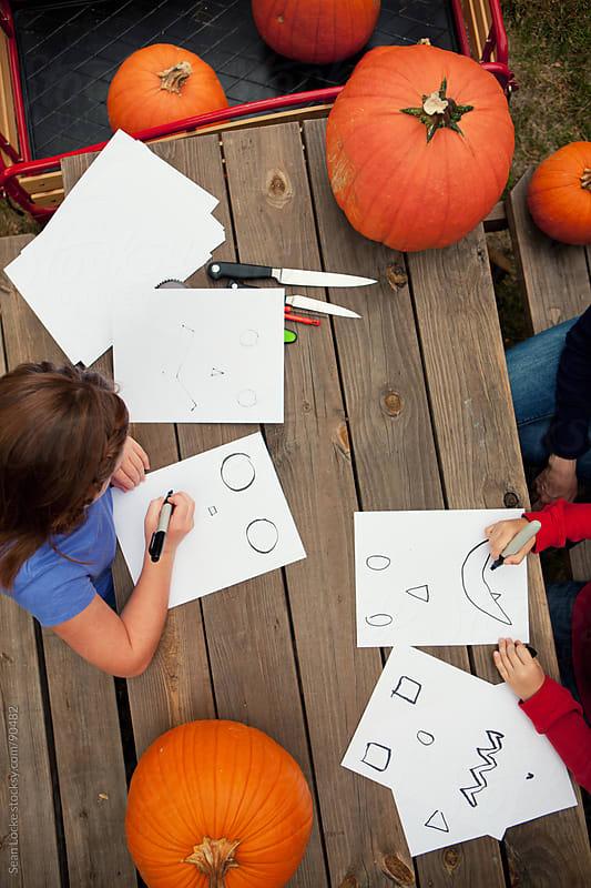 Pumpkins: Kids Work On Making Spooky Faces for Pumpkins by Sean Locke for Stocksy United