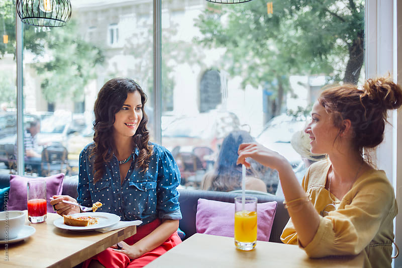 Two Women Sitting and Talking in a Cafe by Lumina for Stocksy United
