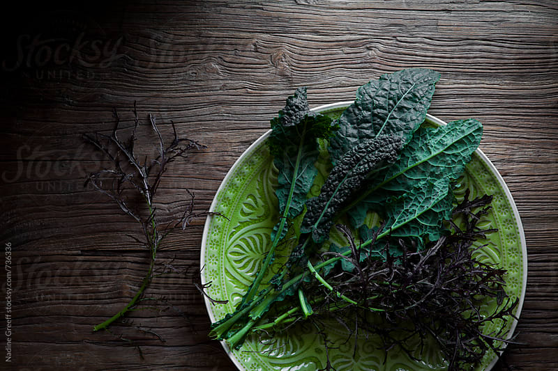 Kale and lettace on wood surface by Nadine Greeff for Stocksy United