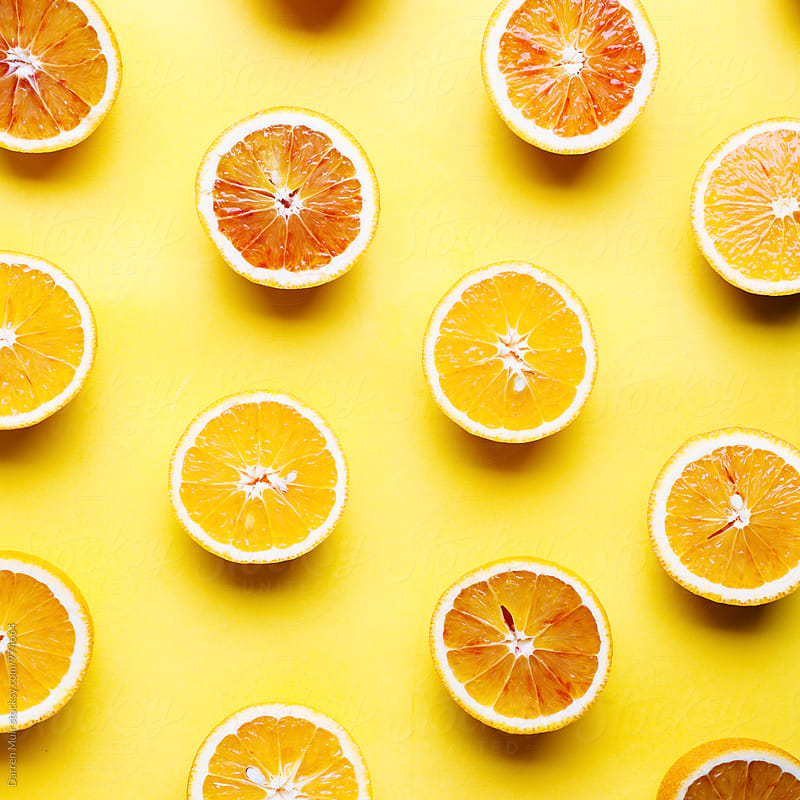 Oranges on a yellow background. by Darren Muir for Stocksy United