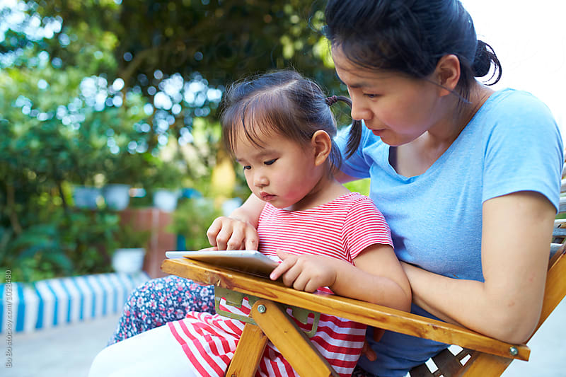 little asian girl using tablet with her mother by cuiyan Liu for Stocksy United