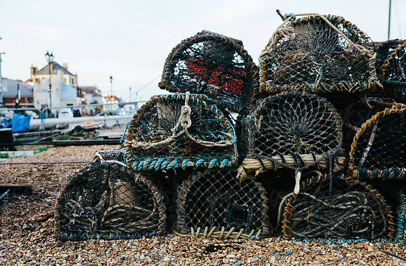 A stack of lobster pots on the beach ready to be loaded onto a fishing boat. by kkgas for Stocksy United