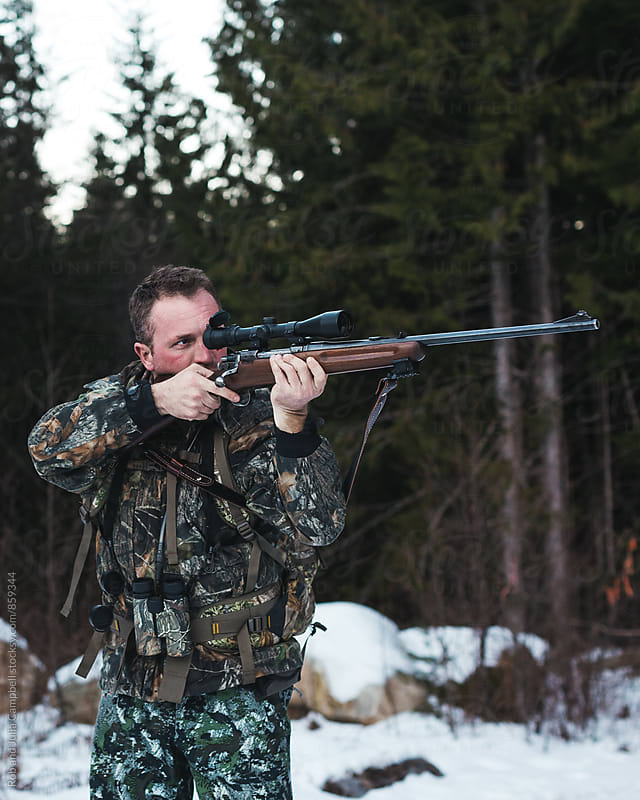 Hunter taking aim with rifle by Rob and Julia Campbell for Stocksy United