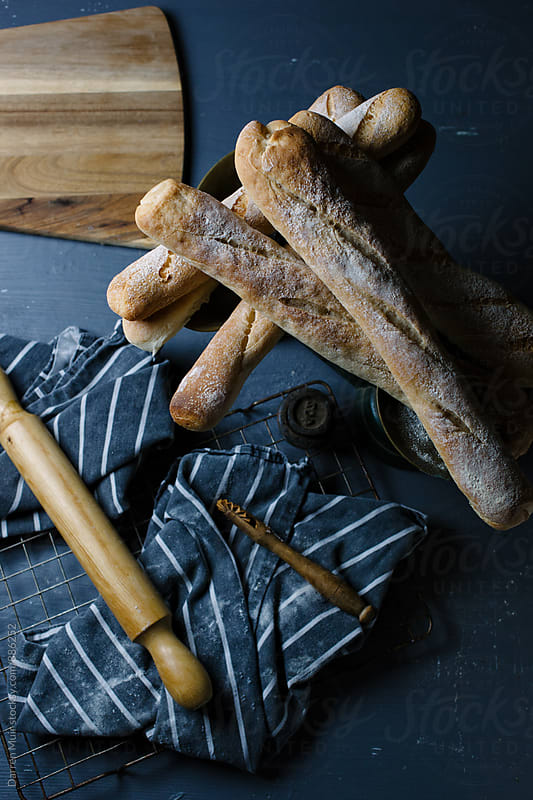 Freshly baked baguettes on kitchen table. by Darren Muir for Stocksy United