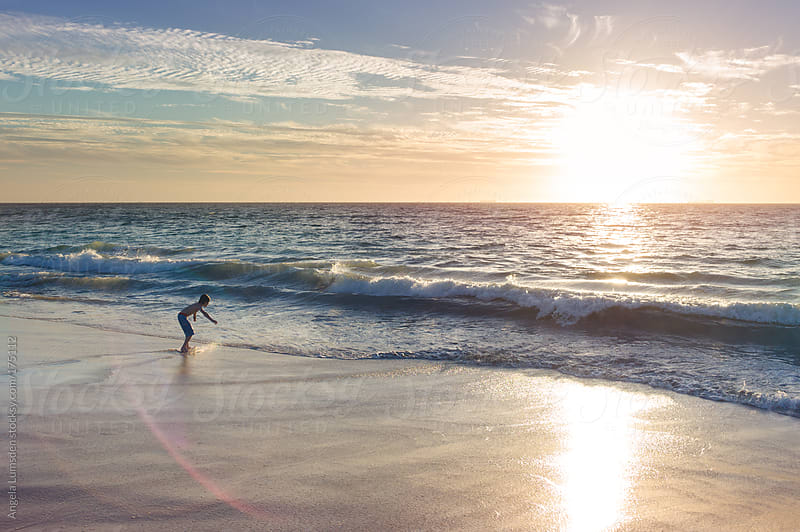 Boy skim boarding at sunset by Angela Lumsden for Stocksy United