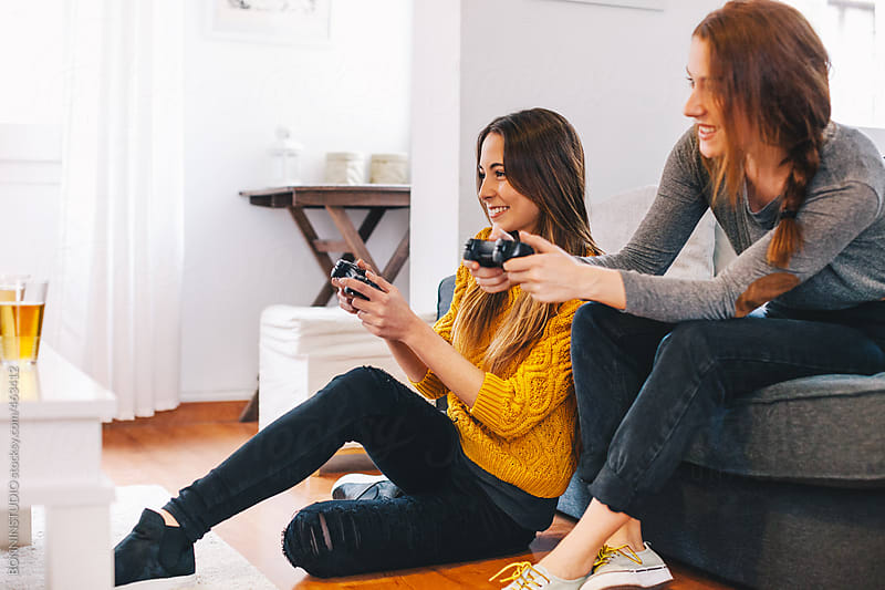 Two happy young female playing video games at home. by BONNINSTUDIO for Stocksy United