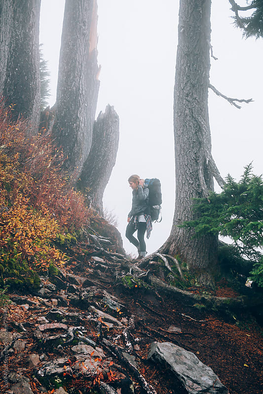 Young Female Backpacker Standing Between Two Trees In Thick Fog Along Trail by Luke Mattson for Stocksy United