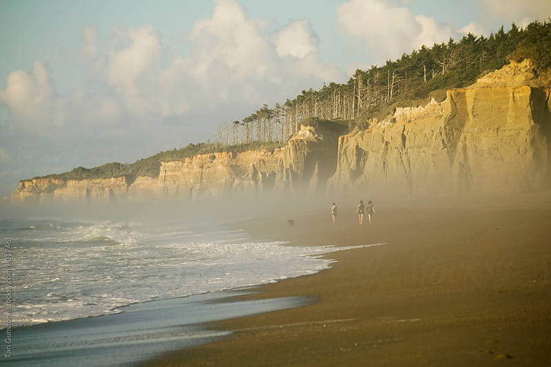 Beach with foggy cliffs in warm sunlight by Tari Gunstone for Stocksy United