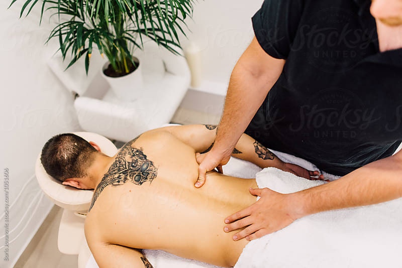 Man enjoying massage treatment indoor by Boris Jovanovic for Stocksy United