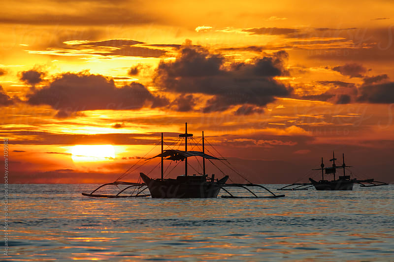Sea sunset with traditional Philippines sail boats by Alejandro Moreno de Carlos for Stocksy United