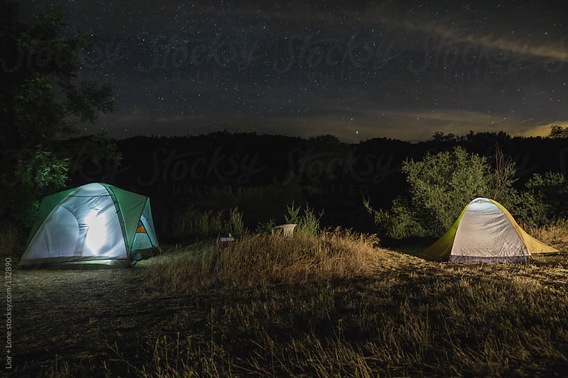 Camping in tents at night under bright sky by Lior + Lone for Stocksy United