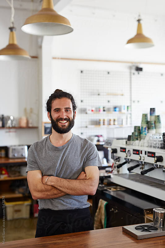 Handsome bearded barista smiling frankly at camera by Martí Sans for Stocksy United