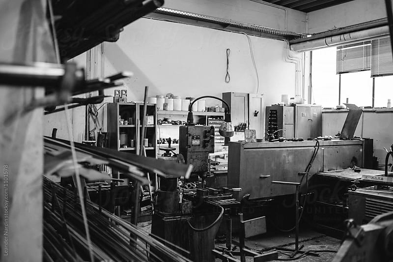 untidy workshop from a metal worker with tools - black and white by Leander Nardin for Stocksy United