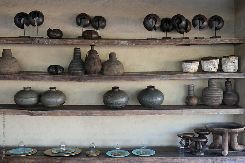 Clay pots and vases on shelves  by Trent Lanz for Stocksy United