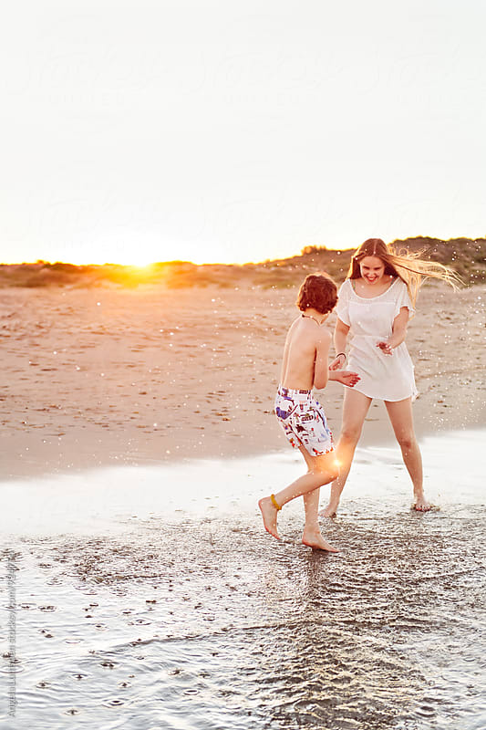 Girl and boy splashing and having fun together at the beach at sunset by Angela Lumsden for Stocksy United
