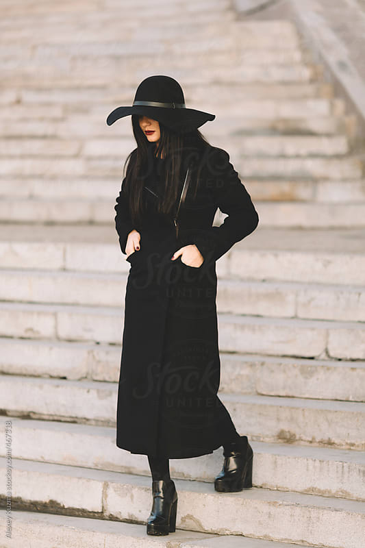 Woman in a black coat and hat walking down . by Alexey Kuzma for Stocksy United