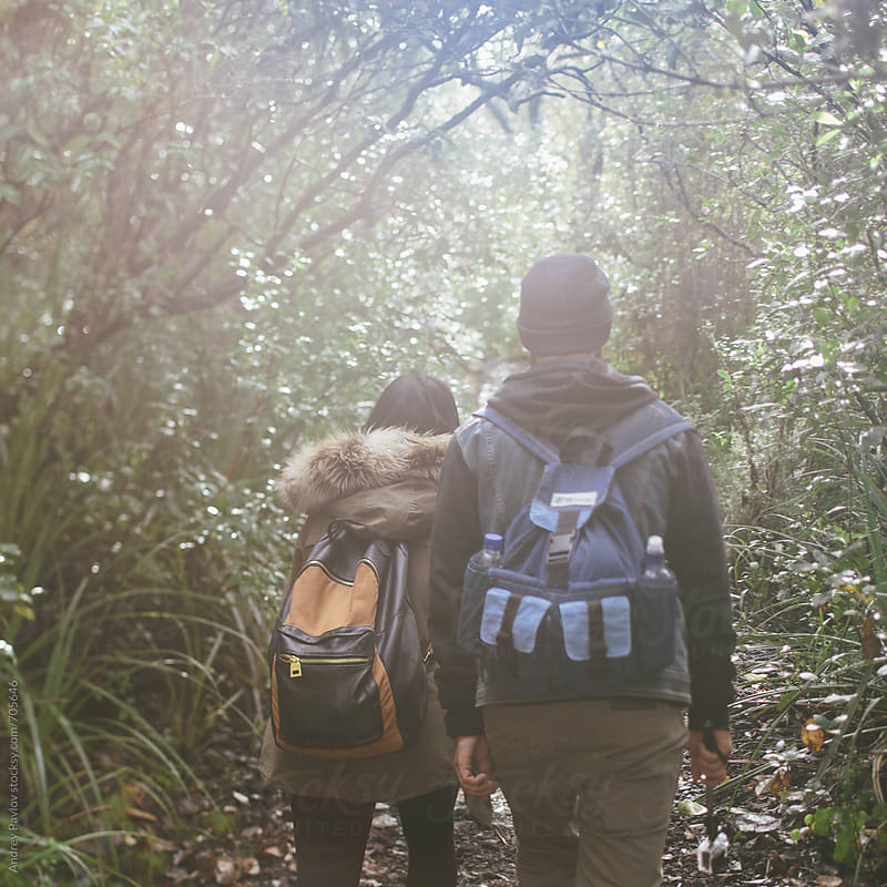 Couple hiking in a forest by Andrey Pavlov for Stocksy United