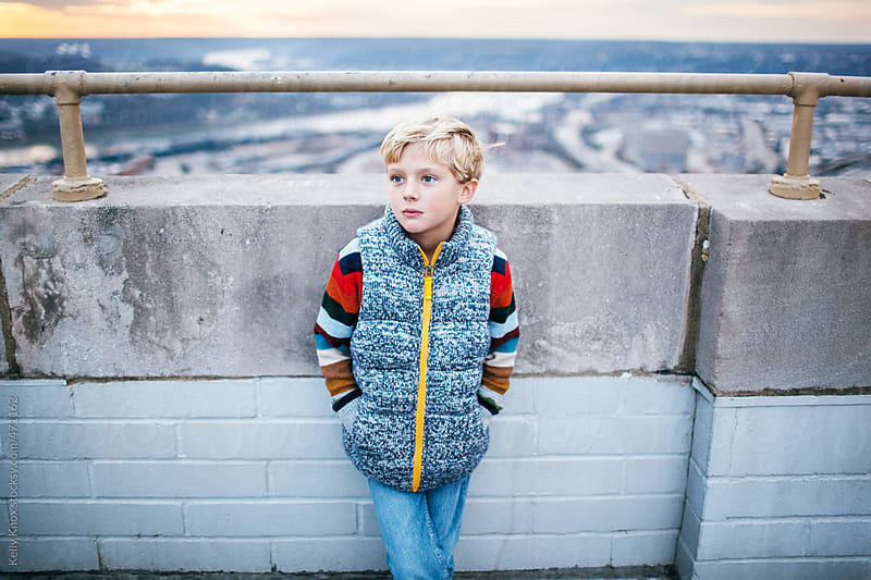 portrait of a serious boy standing against a city wall by Kelly Knox for Stocksy United