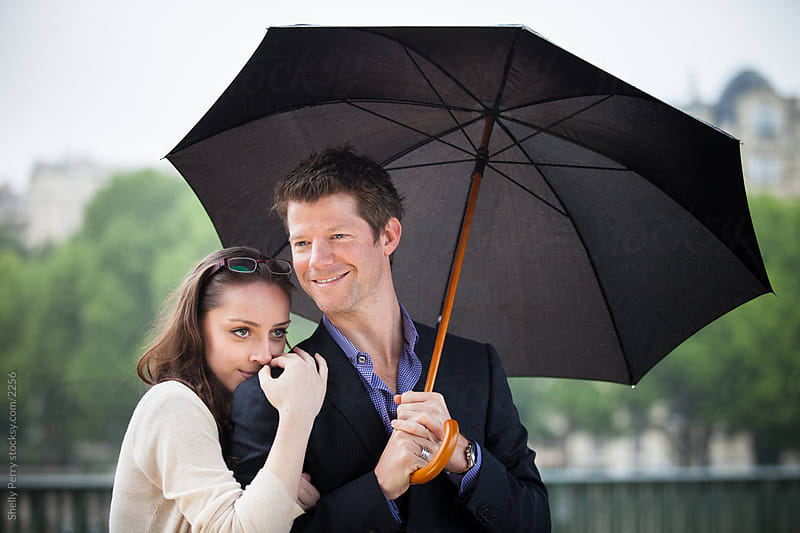 Tourist couple in Paris under an umbrella by Shelly Perry for Stocksy United