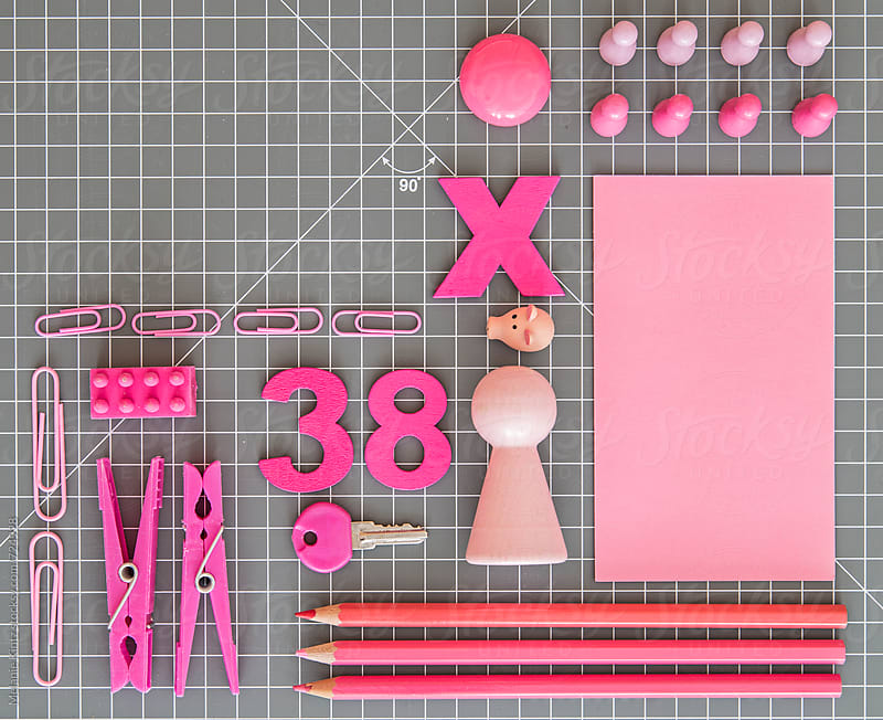 Pink toys and office tools on grey background by Melanie Kintz for Stocksy United
