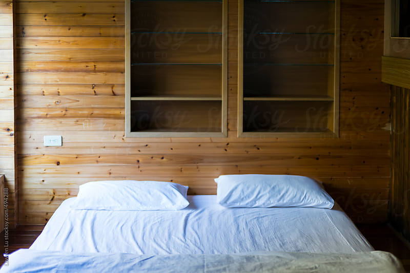 Bedroom with white bedding and wooden wall by Lawren Lu for Stocksy United