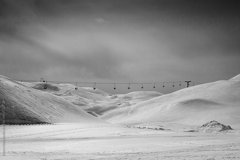Black and white photo of a ski resort on a dark and cloudy day. by Koen Meershoek for Stocksy United