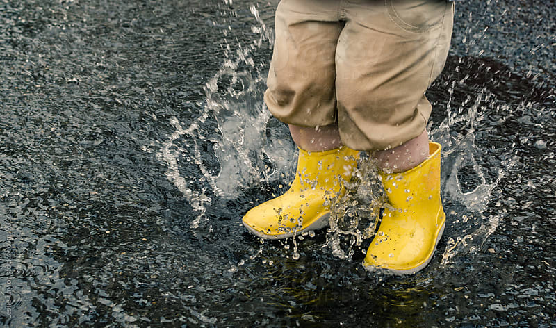 Yellow Boots Splash In A Rain Puddle by Leslie Taylor for Stocksy United