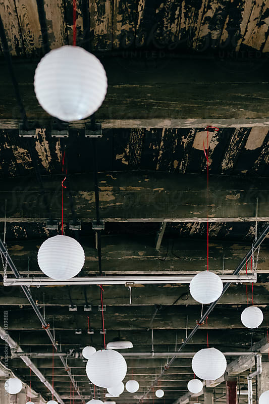 Globe lights hanging from ceiling by Jen Grantham for Stocksy United