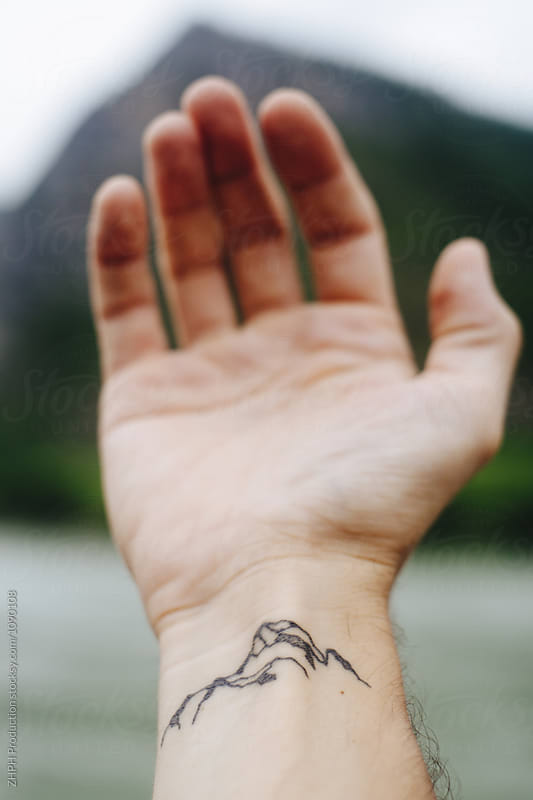 Tattoo and mountain by Artem Zhushman for Stocksy United