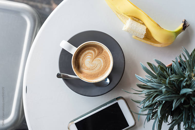 ditch the cake and have a banana with your coffee (sugarless of course), overhead of coffee and phone on a table by Gillian Vann for Stocksy United