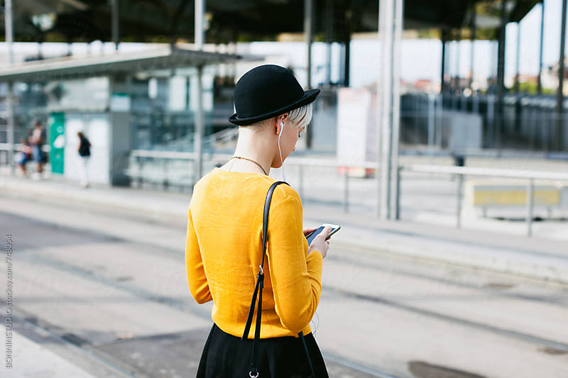 Chic woman using her smartphone waiting on the train station. by BONNINSTUDIO for Stocksy United
