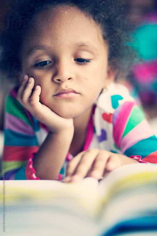 Portrait of young girl in colorful pyjamas reading a book  by anya brewley schultheiss for Stocksy United