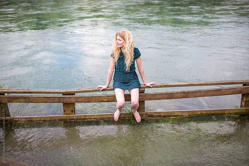 Young woman sitting on a fence along the river by michela ravasio for Stocksy United