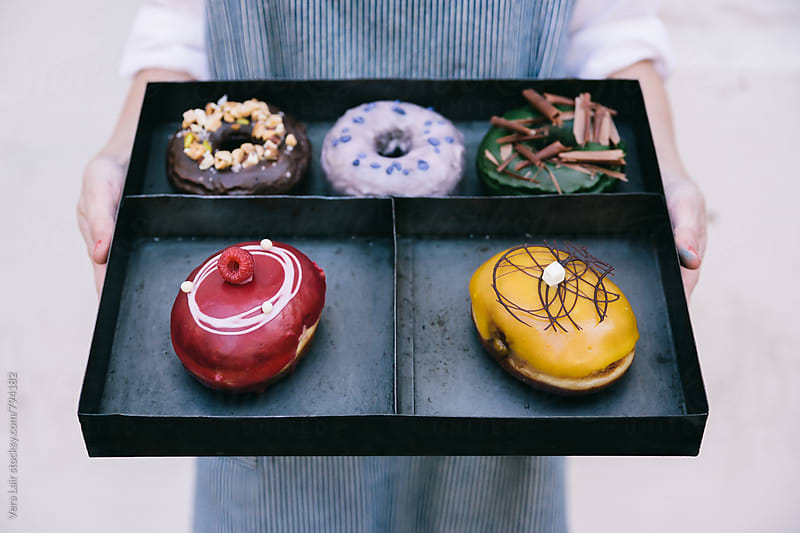 Woman holding a metallic tray with a selection of donuts by Vera Lair for Stocksy United