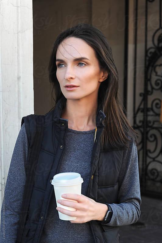 Young woman holding coffee to go. by Liubov Burakova for Stocksy United