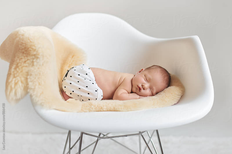 Newborn baby sleeping in a stylish armchair by Lea Csontos for Stocksy United