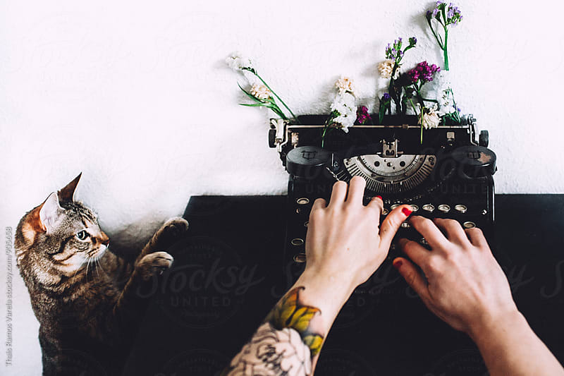 woman typing with a vintage typewriter and cat  by Thais Ramos Varela for Stocksy United