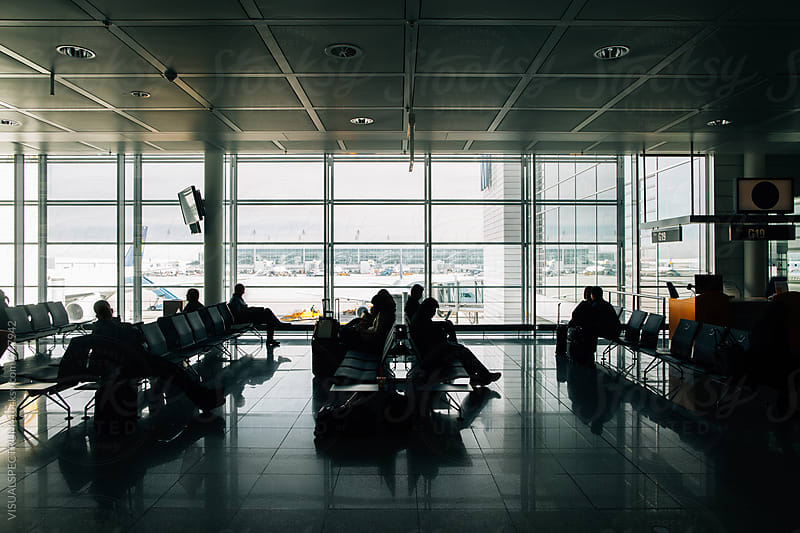Silhouette of Passengers Waiting To Board Plane in Modern Airport by Julien L. Balmer for Stocksy United