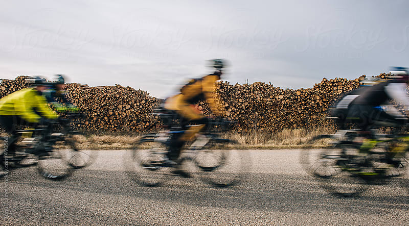 A group of cyclists passing a pile of logs by Tõnu Tunnel for Stocksy United