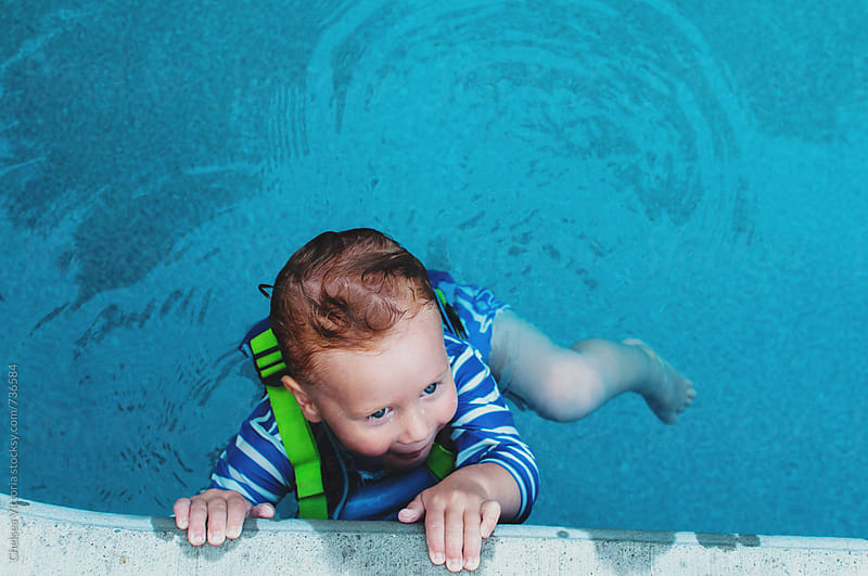 A child swims in a pool by Chelsea Victoria for Stocksy United