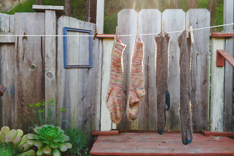 hand knit socks hanging out to dry by Jess Lewis for Stocksy United