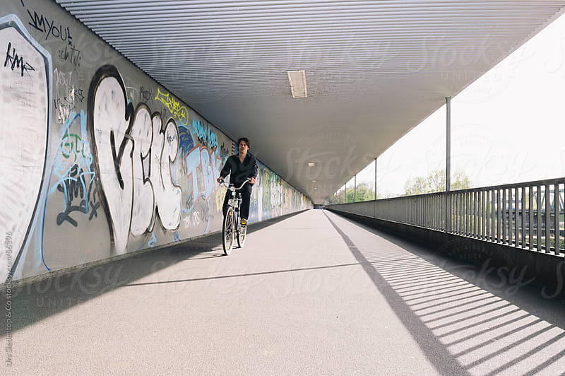 Man on bicycle passing graffiti wall by Urs Siedentop & Co for Stocksy United
